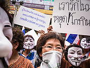 "02 JUNE 2013 - BANGKOK, THAILAND: Anti-government protesters march through Bangkok. The so called White Mask protesters are strong supporters of the Thai monarchy. About 300 people wearing the Guy Fawkes mask popularized by the movie ""V for Vendetta"" and Anonymous, the hackers' group, marched through central Bangkok Sunday demanding the resignation of Prime Minister Yingluck Shinawatra. They claim that Yingluck is acting as a puppet for her brother, former Prime Minister Thaksin Shinawatra, who was deposed by a military coup in 2006 and now lives in exile in Dubai.     PHOTO BY JACK KURTZ"