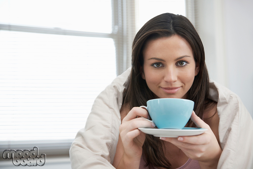 Young woman drinking tea in bed portrait
