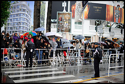 Film Fans wait in the rain on the streets of Cannes as they wait to see film stars to arrive on the Red Carpet during the 65th Annual Cannes Film Festival at Palais des Festivals, Cannes, France, Sunday May 20, 2012. Photo by Andrew Parsons/i-Images.