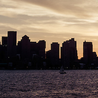 Boston skyline panorama sunset picture with vintage retro tone. Scene includes downtown Boston city skyscraper buildings across Boston Harbor.