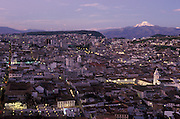 View over the old town of Quito at dusk, with Cayambe volcano in the background