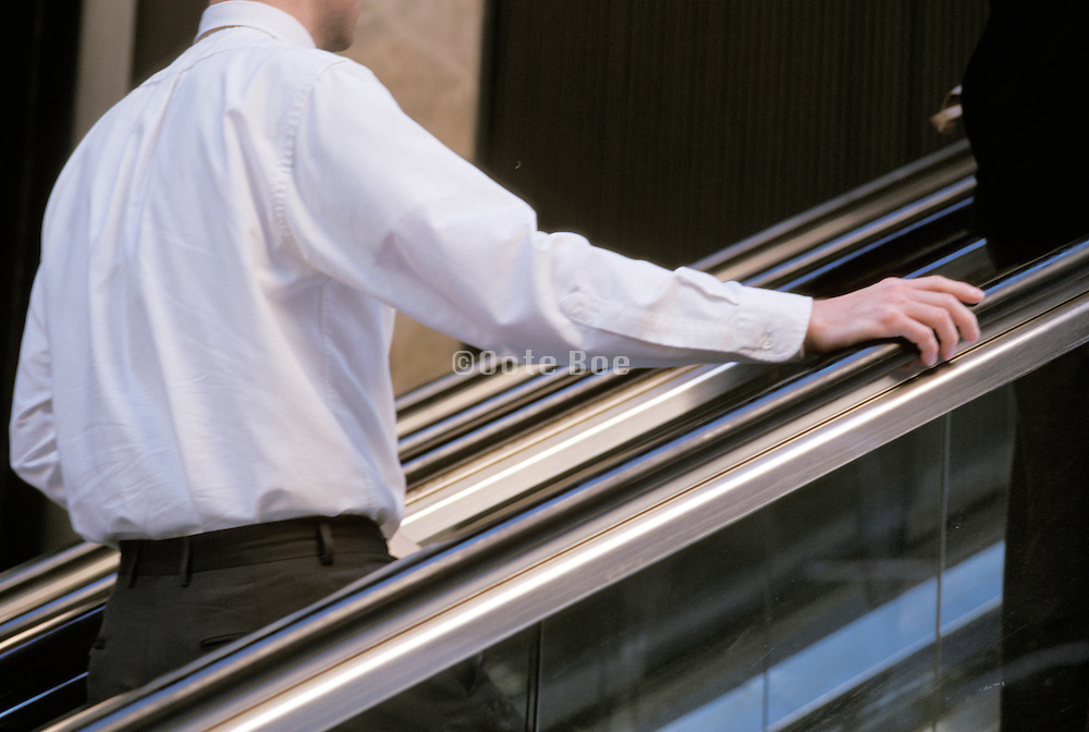 man on escalator going up