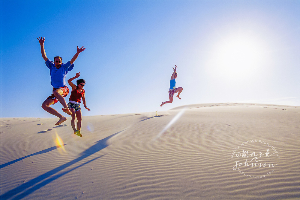 Australia --- People Jumping from Sand Dune