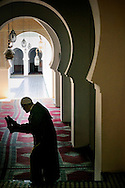 Morocco, Fez. Man entering the mosque and removing his babouches, typical moroccan shoes.