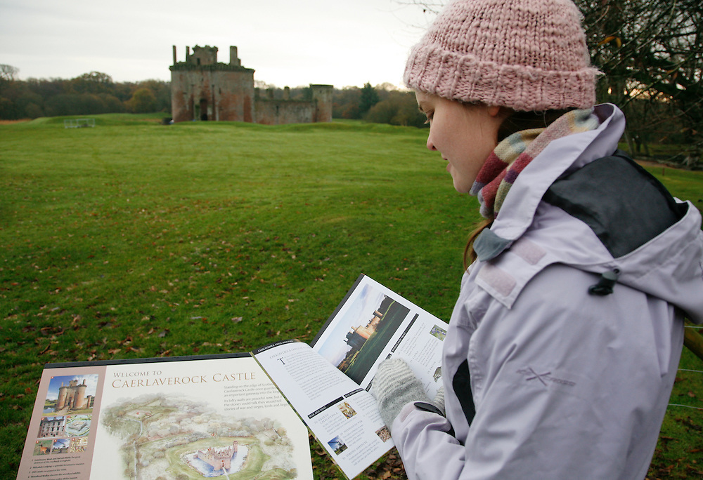 A visitor reads a guide book with Caelaverock Castle in the background.<br /> <br /> Caerlaverock Castle is a moated triangular castle, built in the 13th century, in the Caerlaverock National Nature Reserve area at the Solway Firth, south of Dumfries in the southwest of Scotland. In the Middle Ages it was owned by the Maxwell family. Today, the castle is in the care of Historic Scotland and is a tourist attraction and popular wedding venue. It is protected as a scheduled monument, and as a category A listed building.