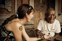 Ketut Liyer, of Eat, Pray, Love fame, gives a palm reading to a western woman on his front porch in Ubud, Bali, Indonesia.