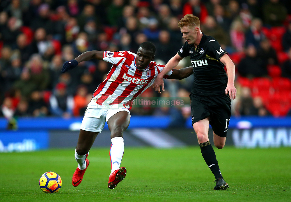 "Stoke City's Kurt Zouma (left) and Swansea City's Sam Clucas during the Premier League match at the Bet35 Stadium, Stoke. PRESS ASSOCIATION Photo Picture date: Saturday December 2, 2017. See PA story SOCCER Stoke. Photo credit should read: Dave Thompson/PA Wire. RESTRICTIONS: EDITORIAL USE ONLY No use with unauthorised audio, video, data, fixture lists, club/league logos or ""live"" services. Online in-match use limited to 75 images, no video emulation. No use in betting, games or single club/league/player publications"