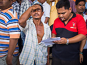 08 FEBRUARY 2014 - PHAWONG, SONGKHLA, THAILAND:  A spectator reacts to losing a wager at a bullfight in rural Songkhla province, Thailand. Bullfighting is a popular past time in southern Thailand. Hat Yai is the center of Thailand's bullfighting culture. In Thai bullfights, two bulls are placed in an arena and they fight, usually by head butting each other, until one runs away or time is called. Huge amounts of mony are wagered on Thai bullfights - sometimes as much as 2,000,000 Thai Baht ($65,000 US).   PHOTO BY JACK KURTZ
