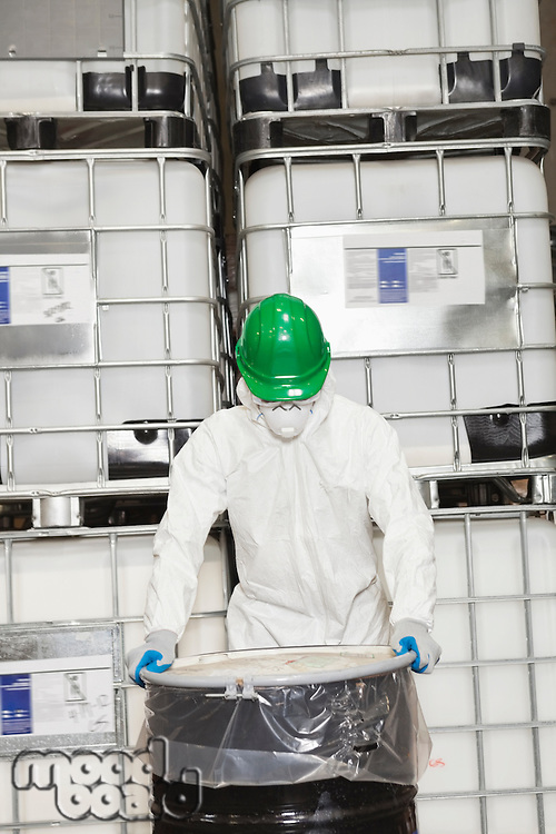 Industrial worker in hazmat suit holding plastic covered chemical drum