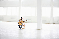 Woman sitting with accoustic guitar in empty warehouse