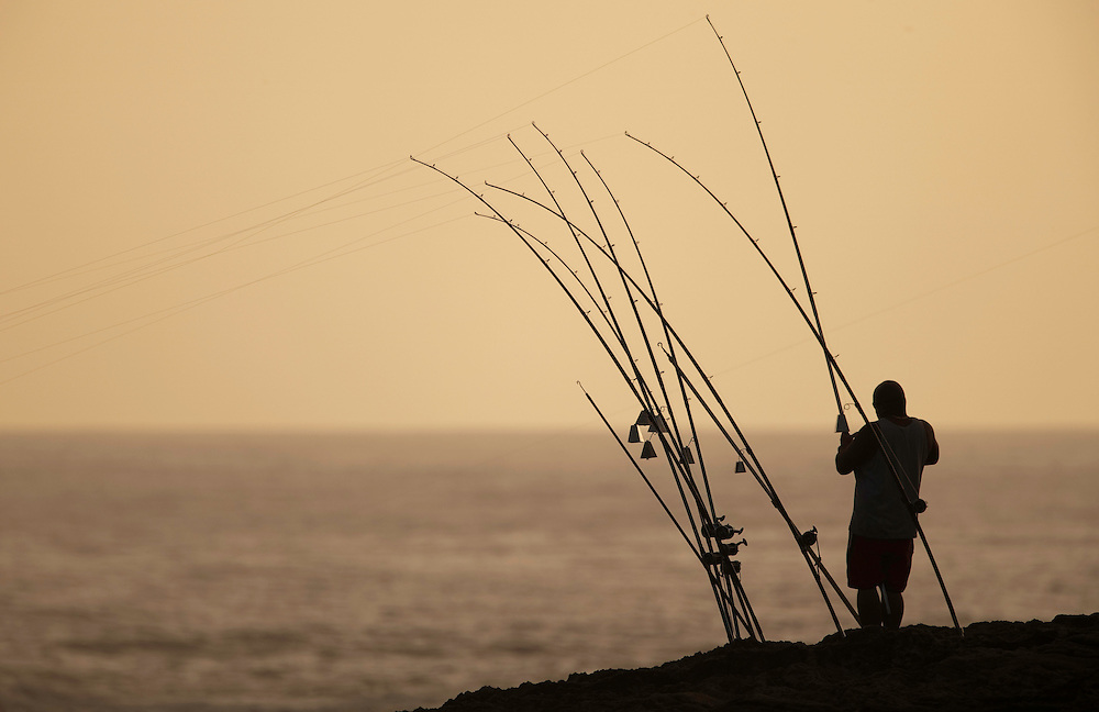 fisherman checking bait, early morning Laie Point