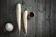 Daikon radish on wooden background, above view.