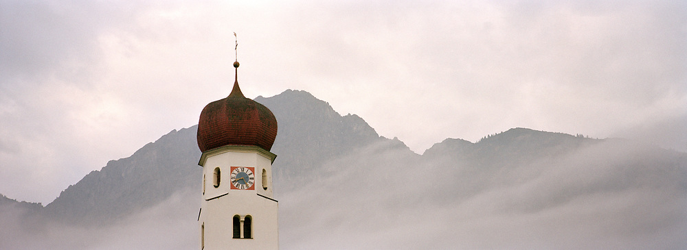 Austria Steeple and Mountains in mist