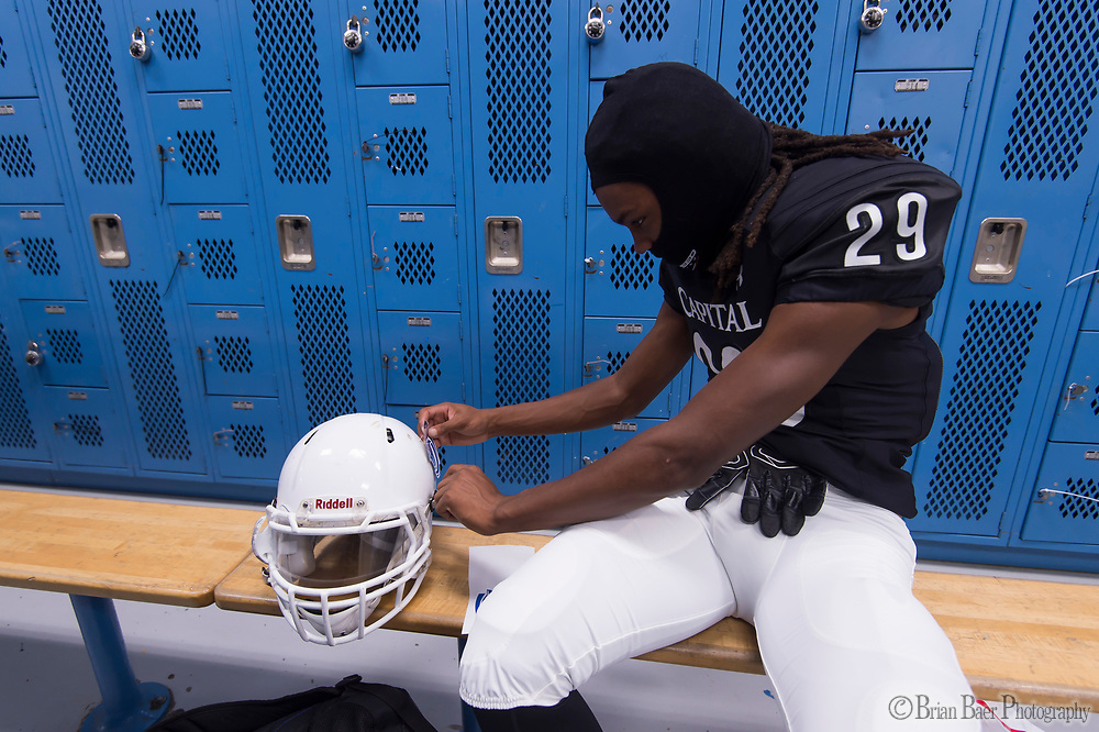 Capitol Christian Cougars Isaiah Bass (29) puts on a helmet decal in the locker room before the game as the Capitol Christian Cougars varsity football team host the Bear River during the first round playoff game, Thursday Nov 9, 2017.<br /> photo by Brian Baer