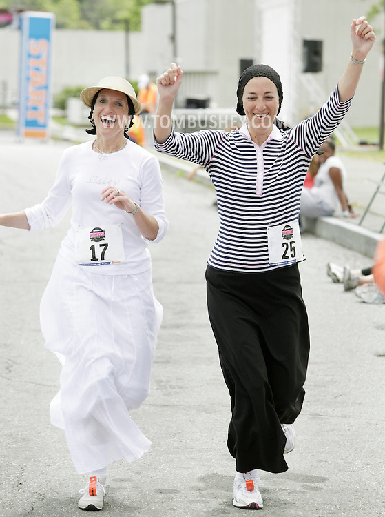 Susan Wachs (17) and Yehudis Brody (25), both of Brooklyn, celebrate as they cross the finish line in the Jrunners 5K Run Walk for Women at Sullivan County Community College in Loch Sheldrake on Wednesday, July 27, 2011.  Many competitors in the race were Orthodox Jewish residents living at summer homes or bungalows in Sullivan County.