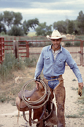cowboy walking with a saddle and lasso on a ranch
