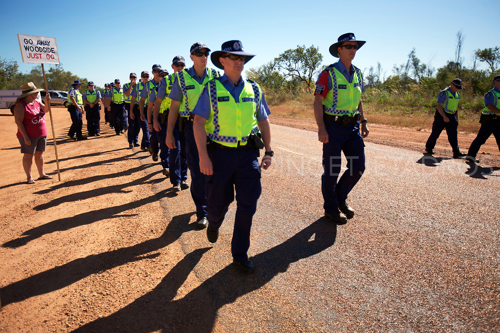 About 30 protesters lined the road as Woodside vehicles, earth moving equipment and personnel proceeded to the site. The group met early this morning at the corner of Cape Leveque Road and Broome Highway...From 9am, a steady stream of about 25 police vehicles arrived, each carrying four or five uniformed officers...Twenty six police from the public order response team formed a line along the road to hold back protesters, while others continued to James Price Point. They were escorted by more police cars with flashing lights. Broome, WA