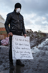 © London News Pictures. Calais, France. 07/03/16. An Iranian man currently on hunger strike stands with a protest sign as police enter the 'Jungle' camp. French authorities are evicting and demolishing the southern half of the Calais 'Jungle' camp, which charities estimate to contain 3,500 people. . Photo credit: Rob Pinney/LNP