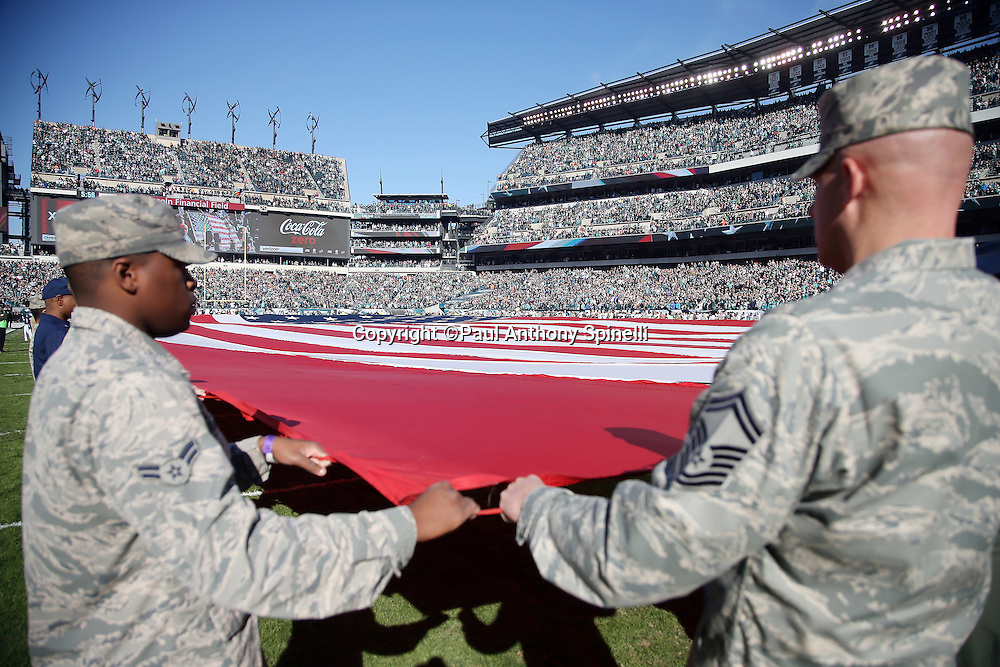 Members of the military hold a large American flag displayed on the field as part of pregame festivities before the Philadelphia Eagles 2015 week 10 regular season NFL football game against the Miami Dolphins on Sunday, Nov. 15, 2015 in Philadelphia. The Dolphins won the game 20-19. (©Paul Anthony Spinelli)