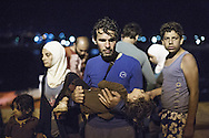 ITALY, Augusta - Immigrants are seen in the port of Augusta (Sicily) after they desembarked from an italian Coast Guard ship who rescued them at sea. on June 16, 2014. A new immigration wave is investing the italian region of Sicily.<br /> <br /> Augusta, Italia - 16 giugno 2014. Circa 400 immigrati sono stati tratti in salvo da alcune unit&agrave; della Capitaneria di Porto nell'ambito dell'operazione Mare Nostrum. I migranti sono sbarcati nel porto di Augusta in Sicilia. Da circa un mese gli sbarchi si susseguono quotidianamente.<br /> Ph. Roberto Salomone