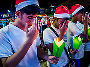 """23 DECEMBER 2018 - CHANTABURI, THAILAND: High school students make the """"sign of the cross"""" at the Cathedral of the Immaculate Conception's Christmas Fair in Chantaburi. Cathedral of the Immaculate Conception is holding its annual Christmas festival, this year called """"Sweet Christmas @ Chantaburi 2018"""". The Cathedral is the largest Catholic church in Thailand and was founded more than 300 years ago by Vietnamese Catholics who settled in Thailand, then Siam.   PHOTO BY JACK KURTZ"""