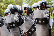 RIot Police await orders to move forward into the UNAH University and begin firing tear gas cannisters into the crowds of protesting students. 10th August 2017.