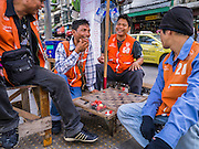 "04 APRIL 2013 - BANGKOK, THAILAND: Motorcycle taxi drivers play checkers while they wait for customers at a taxi stand in Bangkok. Thailand's economic expansion since the 1970 has dramatically reduced both the amount of poverty and the severity of poverty in Thailand. At the same time, the gap between the very rich in Thailand and the very poor has grown so that income disparity is greater now than it was in 1970. Thailand scores .42 on the ""Ginni Index"" which measures income disparity on a scale of 0 (perfect income equality) to 1 (absolute inequality in which one person owns everything). Sweden has the best Ginni score (.23), Thailand's score is slightly better than the US score of .45.   PHOTO BY JACK KURTZ"