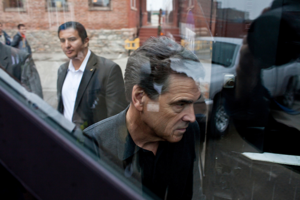 Republican presidential candidate Rick Perry boards his campaign bus after speaking to supporters at a meet and greet at Drake on the Riverfront restaurant on Thursday, December 22, 2011 in Burlington, IA.