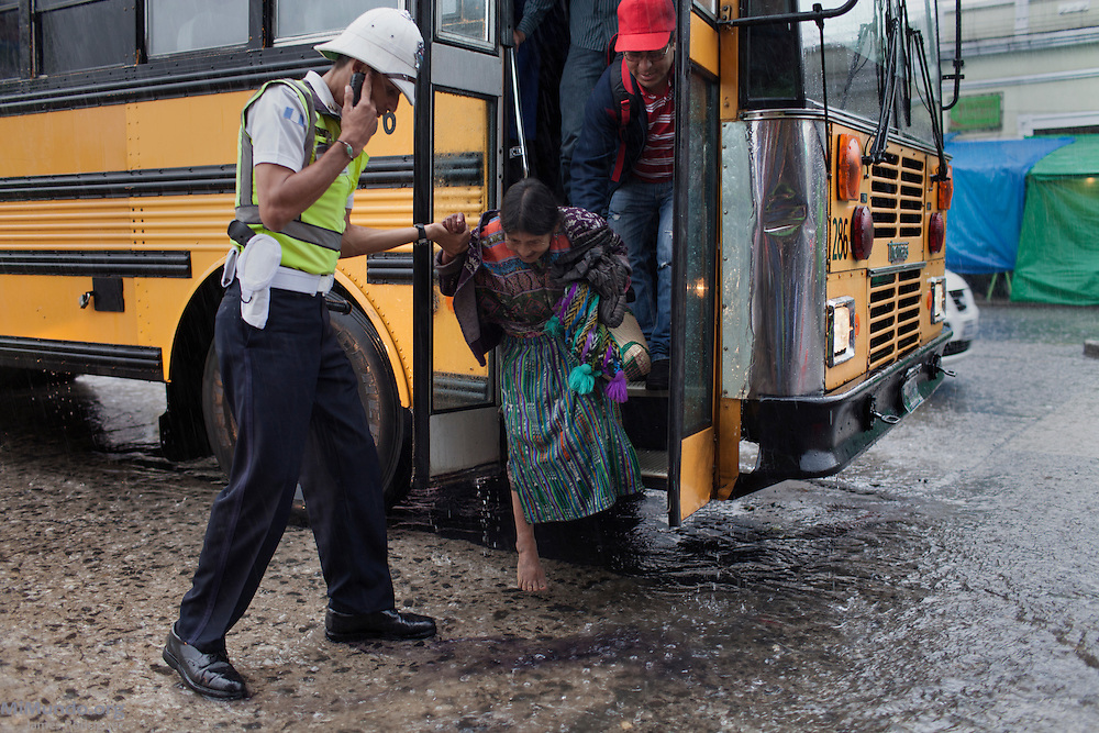 A Municipal Police officer helps a barefoot older woman get off a bus during a rainy afternoon along Guatemala City's 18th street in Zone 1. Guatemala City, Guatemala. August 29, 2014.
