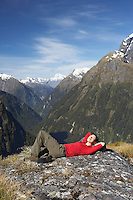 Woman lying on top of mountain peak