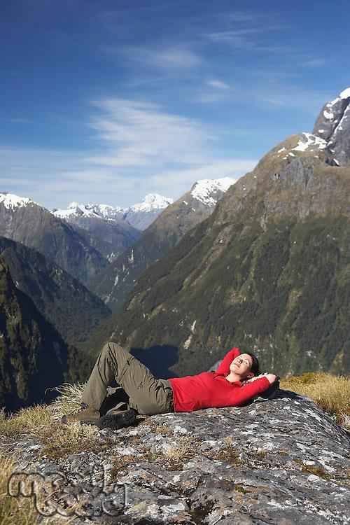 Woman lying on top of mountain peak