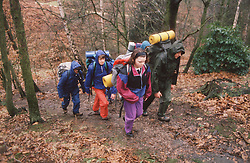 Group of secondary school pupils hiking through woods carrying rucksacks,