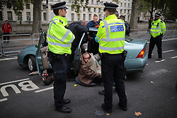 © Licensed to London News Pictures. 07/10/2019. London, UK. Police officers use angle grinders to unlock an Extinction Rebellion protestor locked to a car on Victoria Embankment. Activists will converge on Westminster blockading roads in the area for at least two weeks calling on government departments to 'Tell the Truth' about what they are doing to tackle the Emergency. Photo credit: Rob Pinney/LNP