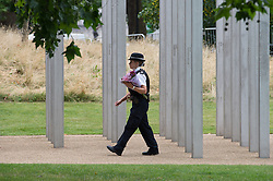 © London News Pictures. 07/07/15. London, UK. A policewoman walks through the 7/7 memorial, ahead of the Memorial Service in Hyde Park to mark the 10 year anniversary of the 7/7 London bombings, Central London. Photo credit: Laura Lean/LNP