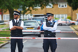 © Licensed to London News Pictures. 20/07/2015 Enfield, UK. Police officers stand at a cordon on Lackmore Road, Enfield after a man died following a stabbing. Police were called to the scene at 18:55hrs on Sunday, 19 July where a 28-year-old man had suffered a stab injury. He died at the scene at 19:31hrs. Three 18-year-old men have been arrested in connection with this incident. Photo credit : Simon Jacobs/LNP