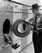 UH OH--Westminster police officer Keith Rock discovers a youngster playing inside a clothes dryer at the East End Laundromat.<br /> (1984 feature photo winner Maryland-Delaware-D.C. Press association)