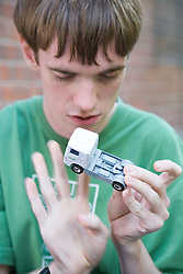 Teenage boy with Autism playing with toy truck,