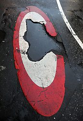 A pothole inside a congestion charge road marking.