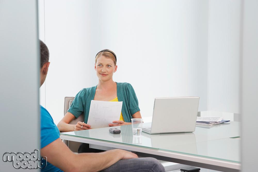 Woman talking to man in office