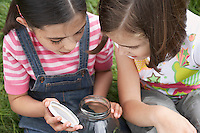 Two girls (7-9) examining jar of insects outdoors