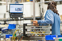 Rear view of female technician repairing computer part in electronics industry
