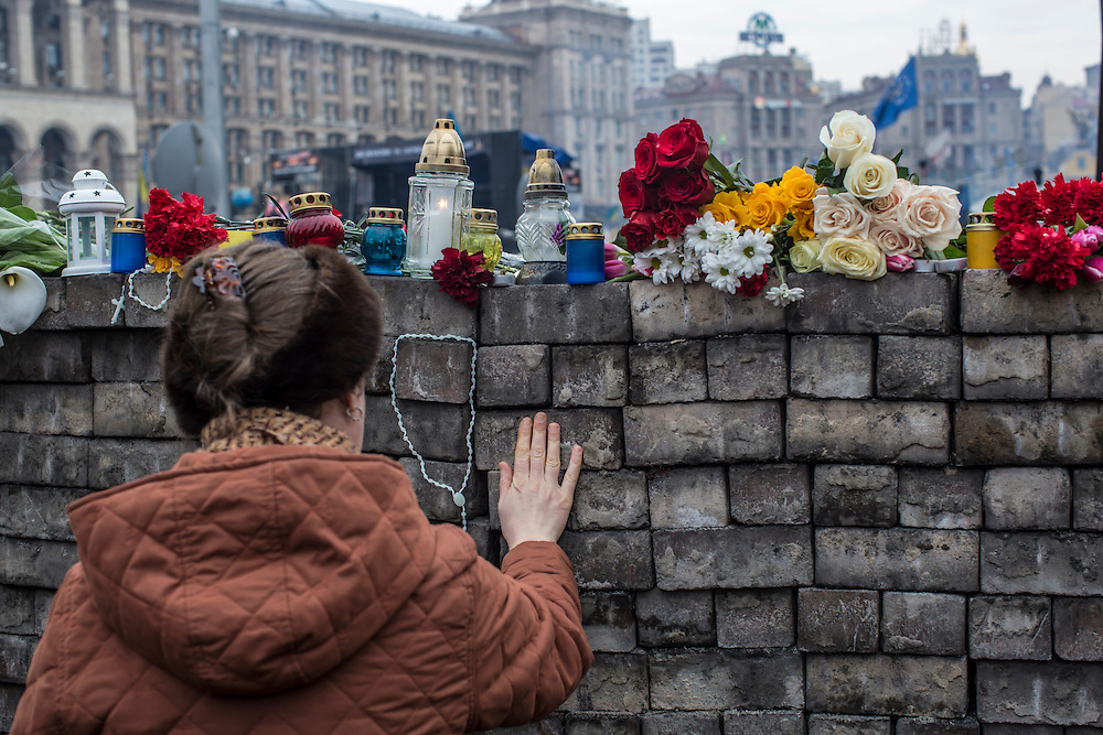 KIEV, UKRAINE - FEBRUARY 23: A woman pays her respects at a memorial to anti-government protesters killed in chashes with police on Independence Square on February 23, 2014 in Kiev, Ukraine. After a chaotic and violent week, Viktor Yanukovych has been ousted as President as the Ukrainian parliament moves forward with scheduling new elections and establishing a caretaker government. (Photo by Brendan Hoffman/Getty Images) *** Local Caption ***
