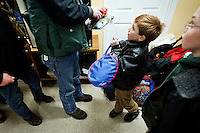 Judah Lamb, 6, presents a bag to one of the Fresh Start patrons Friday morning after Lamb and his family delivered 50 bags filled with clothing and toiletry items and 100 gifts to the drop-in center in downtown Coeur d'Alene.