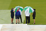 The covers are on and the umpires are on the field with umbrellas up as rain looks like it will delay the start of play during the International Test Match 2019 match between England and Australia at Lord's Cricket Ground, St John's Wood, United Kingdom on 18 August 2019.