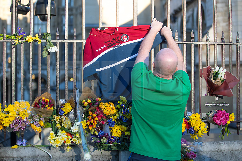 © Licensed to London News Pictures . 25/03/2017 . London , UK . Ian Long from Peckham ties a Charlton Athletic football shirt to railings outside Old Palace Yard at the Houses of Parliament with a tribute to murdered policeman Keith Palmer written across the chest . PC Palmer is understood to have been a regular supporter at Charlton matches . Photo credit : Joel Goodman/LNP