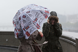 © Licensed to London News Pictures. 26/08/2014. London, UK. Tourists with umbrellas on Tower Bridge during heavy rain and strong wind. Heavy rain and cold weather are forecast for the rest of the day. Photo credit : Vickie Flores/LNP
