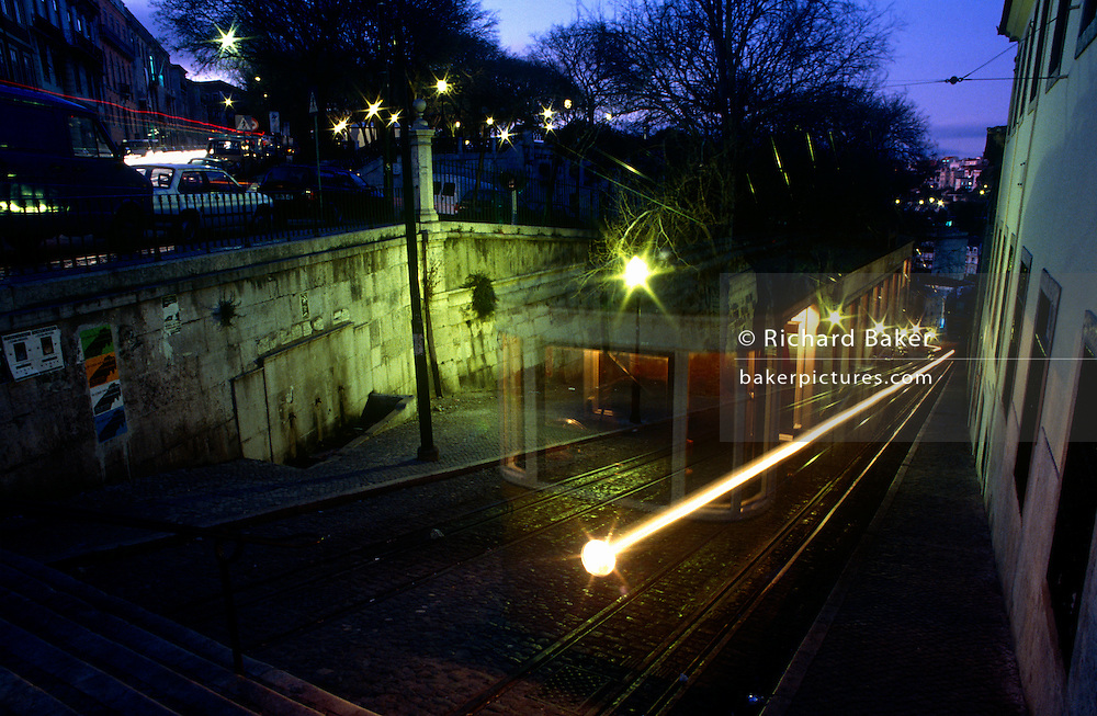 A funicular tram blurs at night as it descends the steep and cobbled Elevador de Gloria in Lisbon's Biarro Alto district.