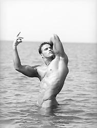 bodybuilder posing in the ocean