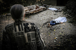 An old woman passes bodies of dead local residents near a damaged block of flats after Ukranian army shelling in downtown of Donetsk, Ukraine, 23 August 2014. Residential areas in several districts of Donetsk, including the central part of the city, suffered from artillery fire, five people was killed and 15 wounded, the press centre of Donetsk city Council reported.