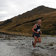 Runner Paul Hellebrekers crosses  Moke Creek on the Ben Lomond High Country Station during the Pure South Shotover Moonlight Mountain Marathon and trail runs. Moke Lake, Queenstown, New Zealand. 4th February 2012. Photo Tim Clayton